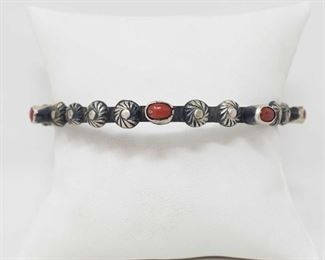 155 Artist Marked Native American Sterling Silver and Coral Stone Bangle Bracelet Artist Marked Sterling Silver and Coral Stone Bangle Bracelet Weighs approx 30.4g Low Estimate: 120.00 High Estimate: 200.00