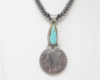 """173: Beautiful Artist Marked Sterling Pendent with a Authentic Morgan Silver Dollar (chain not included)  Beautiful Artist Marked Native American Sterling Pendent with a Authentic Morgan Silver Dollar Chain not Included Weighs approx 39.5g Measures approx 3"""" Low Estimate: 250.00 High Estimate: 400.00"""