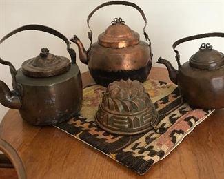Antique copper tea kettles and a copper mold.