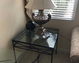 Many wrought iron and glass side tables and coffee tables