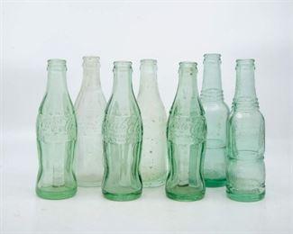 Lot 118. Seven vintage Coca-Cola bottles and Nu Grape glass bottles.