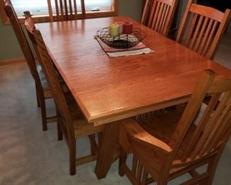 Mission style dining room table and chairs with leaves tucked underneath