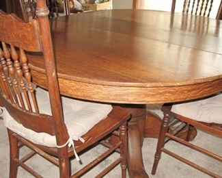 Antique round oak table and set of five oak pressed back chairs.