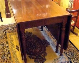Cherry drop leaf gate leg extension table with three leaves and pads.