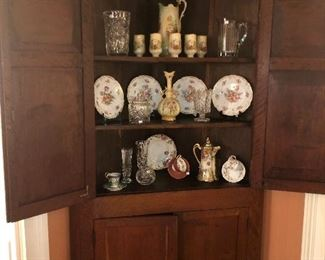 19c KY LBL cherry corner cabinet with popular as the secondary wood.  Collection of Dresden plates, vase, cup and saucer, German hand-painted rum set, Waterford, Shannon Crystal, English bone china and more.
