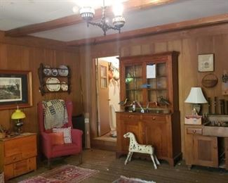 Left to right: grandfather clock, sugar chest, wing chair, stepback cupboard, primitive horse, dry sink