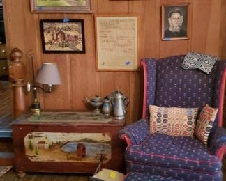 Painted chest, wing chair and ottoman, Asian rug in foreground, woven coverlet pillows