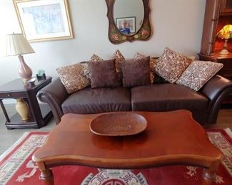 Very Pretty Area Rug. Leather Couch with Throw Pillows, Coffee Table, End Table & Lamp, Mirror, Art