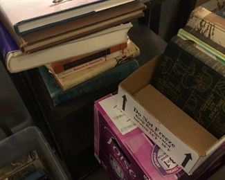 Books , box of magazines and an open back book shelf.