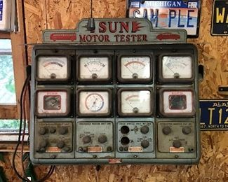 """Vintage motor tester is one of the items lining the walls of a mechanics """"man cave""""."""