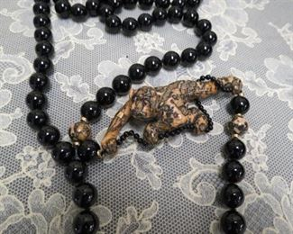 One of a kind black onyx bead necklace with 14k gold spacers carved stone monkey pendant.