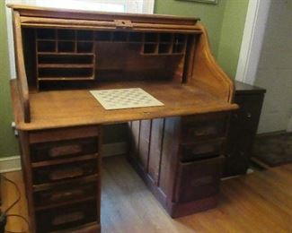 Oak desk with 3 or 4 drawers for storage. One drawer is file size.  It has a roll top.