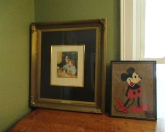 The mickey mouse framed piece is made of felt. The print shows a mother and child.