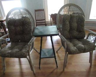 Pair of wicker chairs with chair pads.  The Pine table between the chairs is painted green and has a lower shelf.
