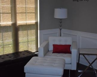 "White leather Chair and matching Ottoman with ""Tufted"" accents, floor lamp and one of at least 2 Matching End Tables. In the left background is a Tufted Leather Storage Bench"