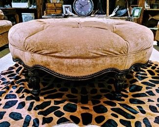 large round tufted ottoman and animal print cowhide rug