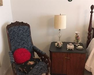 Antique Rocking Chair,1 of a pair of Nightstands,Lamp, Capodimonte Porcelain Flowers,Needlepoint Chair Covers,Pillow.