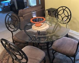 iron and glass kitchenette table and chairs and nice round rug