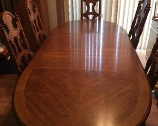 Dining table includes 2 leaves and 6 chairs in total.  5 side and 1 arm chair