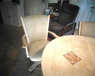 Detail of one of the kitchen table chairs, with arms and is on wheels
