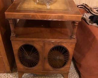 """Weiman Mahogany & Leather Top End Tables, Solid wood construction, tooled leather tops, 2 swing cabinet doors with metal sunburst grills, tops raised on column supports, finished backs, great American craftsmanship. Early to Mid 1900s, American 27"""" H x 18"""" W x 22.5"""" D"""