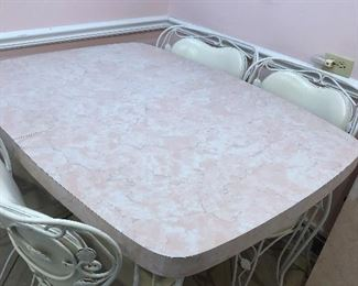 Pink Laminate Vintage Kitchen table with one extension wrought iron heavy legs and chairs with white vinyl cushions barely used.