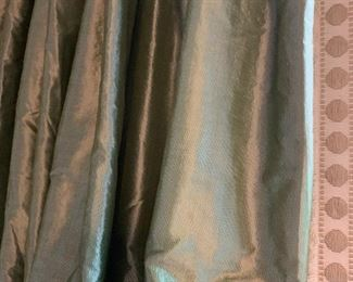 A close up of the green silk drapes hung on two windows