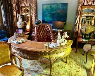 The large circular desk is flanked by a pair of brown temple jars and a pair of French mirrors, the desk chair is from Hickory Chair Company