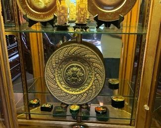 The contents of the display cabinet are as follows: top shelf two fowl plates by Royal Vienna and a pair of as is ivory cuttings. The next two shelves hold a collection of Russian Lacquer boxes.