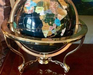 A large stone globe containing many semi  precious stones