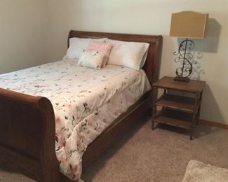 Oak queen size sleigh bed, bamboo-style side table, and metal lamp