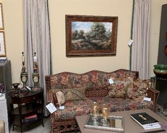 Pair of Drapery panels Antique wicker sofa  Assorted pillows Oval mahogany end table Pair of painted lamps Large antique, framed Oil painting