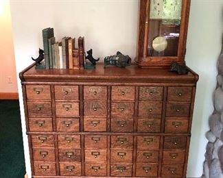 Antique library filing cabinet; sampling of the antique books and bookends for sale; antique clock.