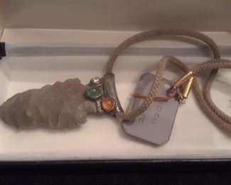 Unusual arrowhead necklace with diamond, royal topaz, and cabachon green garnet on a woven silk cord.