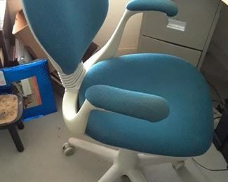 Turquoise ergonomic chair with white frame is unusual