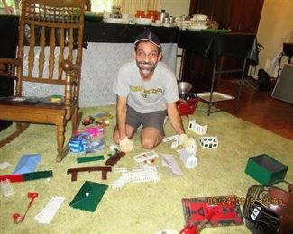 OUR OWN MANNY PUTTING TOGETHER THE PLASTICVILLE HOUSES,  WE DO HAVE FUN SETTING UP THESE SALES