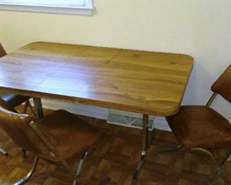 Vintage faux-wood-grain and chrome  kitchen table with three matching vinyl-covered chairs.