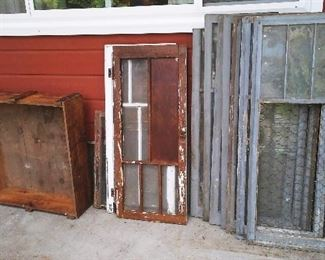 A selection of vintage windows and frames with loads of old paint patina and a large vintage shipping crate.