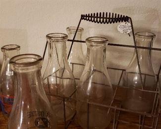 Antique wire milk carrier, plus several old milk bottles