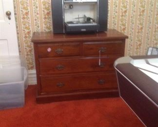 Vintage turntable with fold out speakers on low chest of drawers