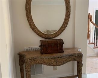 Wood console table with carvings and oval mirror