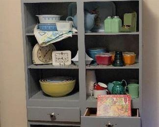 Cabinet with vintage Tinker Toys, wooden coffee grinder, vintage Pyrex, Jadite salt and pepper