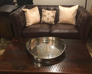 Leather Macy's Chesterfield tufted loveseat man cave. Silver serving tray, pillows, hammered distressed coffee table, lamps, decor, artwork
