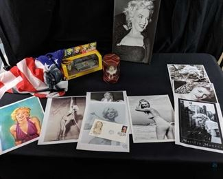 "Marilyn Monroe Lot of Collectibles- 1. 3'x5' Marilyn flag, A 10""x15"" mounted photo, A Ford Thunderbird and Marilyn figure 2. 8 prints in the folder; 32 cent stamp canceled by Universal Studios, 1995; Heirloom Ornament of ""The Seven Year Itch"" pose - dated 1998."