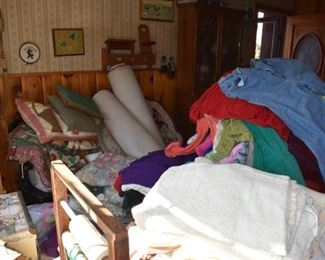 lots of quilts, pillows, farmhouse Americana, and a really cool shaker/farmhouse spindle bench under all the pillows!