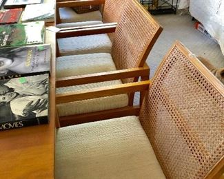Set of four MCM cane arm dining chairs.