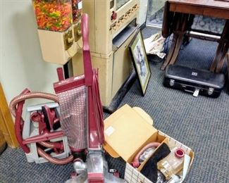 Kirby Vacuum w/ accessories and more accessories in Box       A vintage Candy Machine  Part of another Vintage machine ..( Black case w/ Trumpet sold)    AND  a side view of Duncan Phyfe Table  At site Saturday