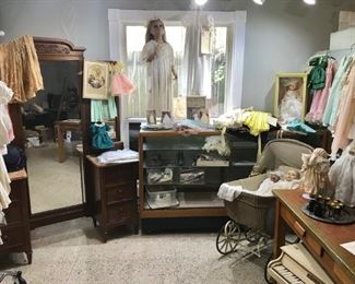 Christening garments - from 19th century on, vintage children's clothing, doll clothing, many dolls (porcelain, rubber), Victorian golden oak vanity, mannequins, commercial display and folding mirror, excellent oak work table, Hummels, vintage stroller, and more just in one photo!