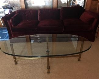 Maroon couch; glass & brass table