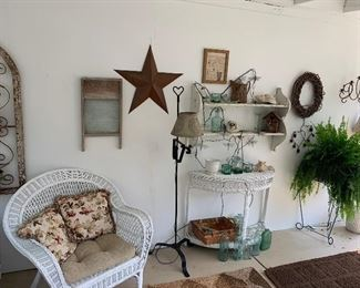 137- Country style iron and wood wall plant holder, vintage washboard, rusted metal wall star, iron floor lamp, wicker furniture, decorative glass bottle, wreath, live fern and plant stand